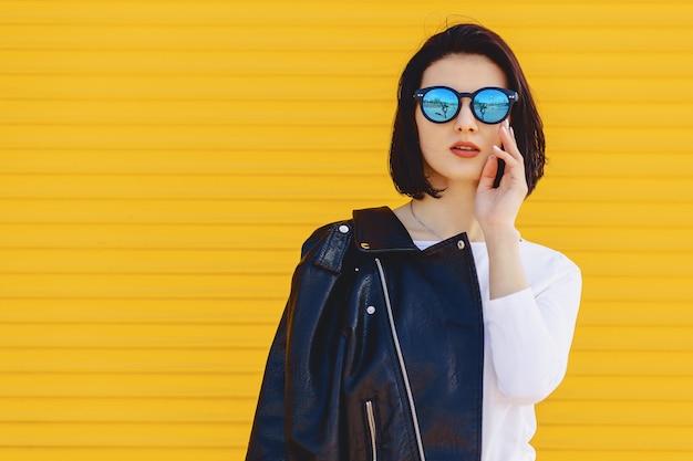 Gafas de sol hermosas de la muchacha en fondo amarillo brillante Foto Premium