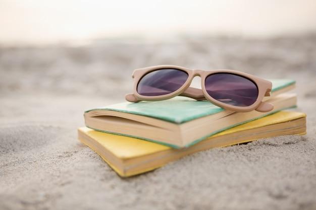 Gafas de sol y libros sobre la arena Foto gratis