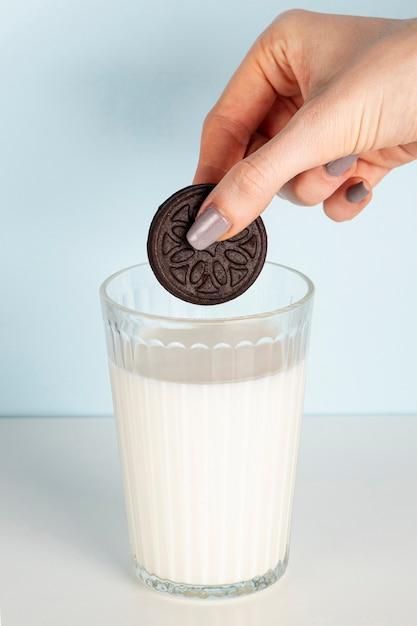 Galleta sostenida por encima del vaso de leche a largo plazo tiro Foto gratis
