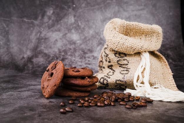 Galletas al horno y granos de café tostados con saco sobre fondo rústico Foto gratis