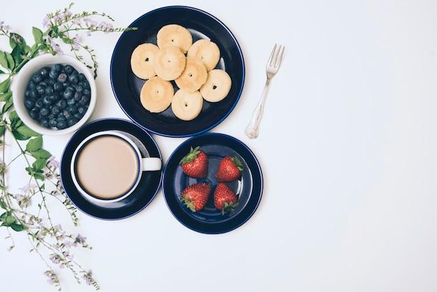 Galletas; arándanos; café y fresas sobre fondo blanco. Foto gratis