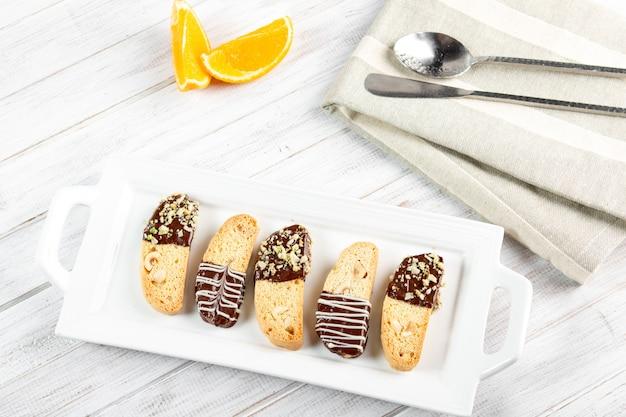 Galletas cantuccini. galleta italiana del biscotti en la placa blanca en un fondo de madera blanco. vista superior. Foto Premium