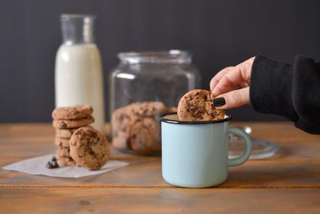 Galletas con chispas de chocolate en un frasco de vidrio con una botella de vidrio de leche y una taza de esmalte turquesa sobre un fondo rústico de madera con una mano de mujer sosteniendo una galleta Foto Premium