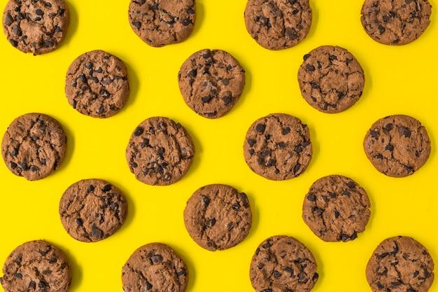 Galletas de chocolate al horno sobre fondo amarillo Foto gratis