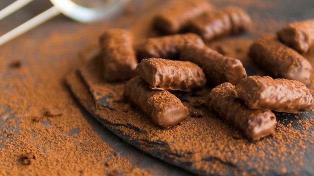 Galletas de chocolate glaseadas cubiertas con cacao en polvo en un plato negro Foto gratis