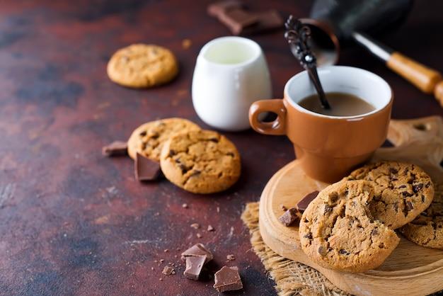 Galletas de chocolate en plato y taza de café caliente Foto Premium