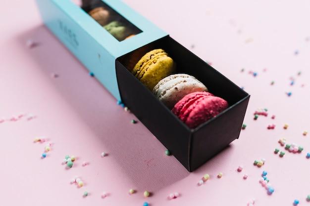 Galletas coloridas de los macarrones en una caja en un fondo rosado Foto gratis