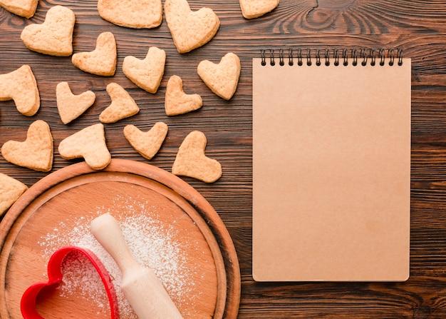 Galletas del día de san valentín en forma de corazón con cuaderno Foto gratis