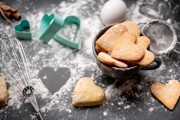Galletas del día de san valentín con harina y utensilios de cocina. Foto gratis