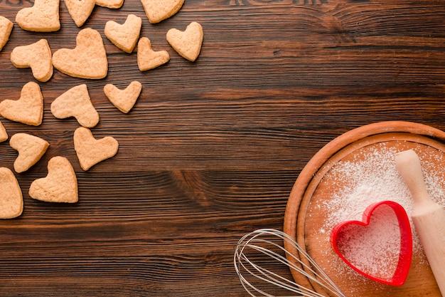 Galletas del día de san valentín con utensilios de cocina sobre fondo de madera Foto gratis