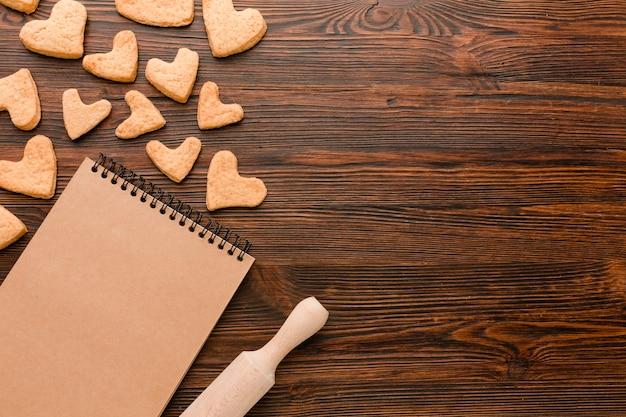 Galletas en forma de corazón para el día de san valentín con cuaderno y rodillo Foto gratis