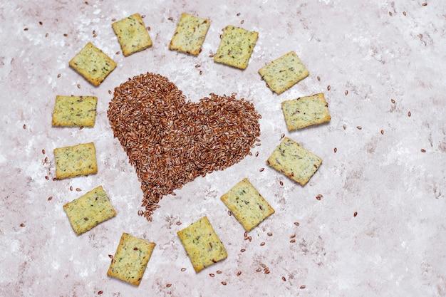 Galletas en forma de corazón de semillas de lino con aceite de oliva, semillas de lino y verduras, vista superior Foto gratis