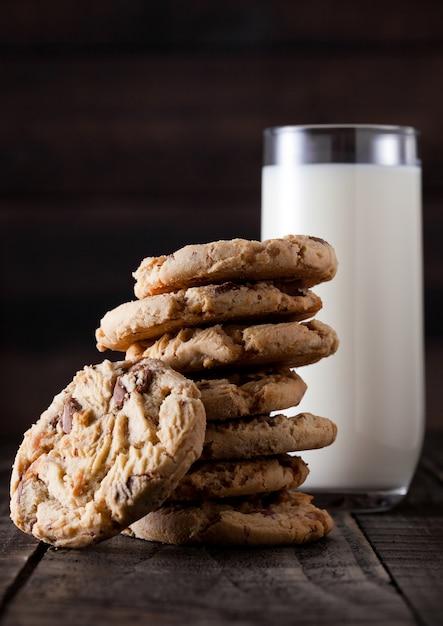 Galletas sin gluten de caramelo dulce avena sobre fondo de madera vieja con vaso de leche Foto Premium