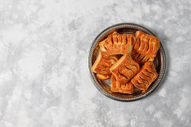 Galletas de hojaldre rellenas de mermelada de manzana y manzanas rojas frescas sobre hormigón ligero Foto gratis