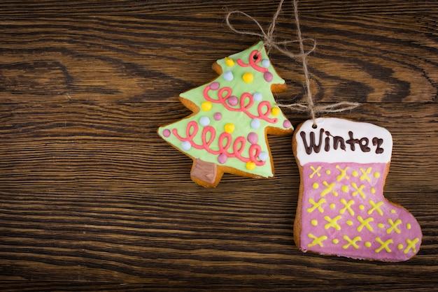 Galletas de jengibre colgando sobre madera. vista superior de decoraciones de navidad con espacio de copia. prepárese para la víspera de navidad u otras vacaciones de invierno. Foto Premium