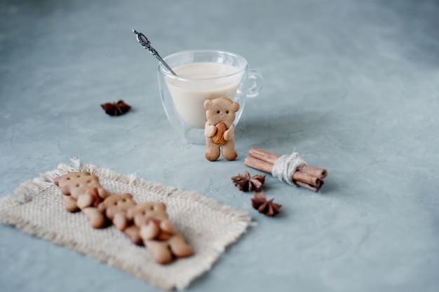 Galletas de jengibre con forma de osos con almendras con palitos de canela y ponche de huevo Foto Premium