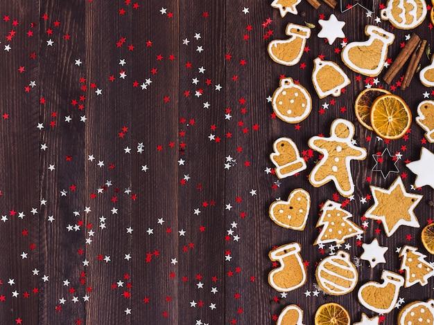 Galletas de jengibre navidad año nuevo naranjas canela en mesa de madera Foto gratis