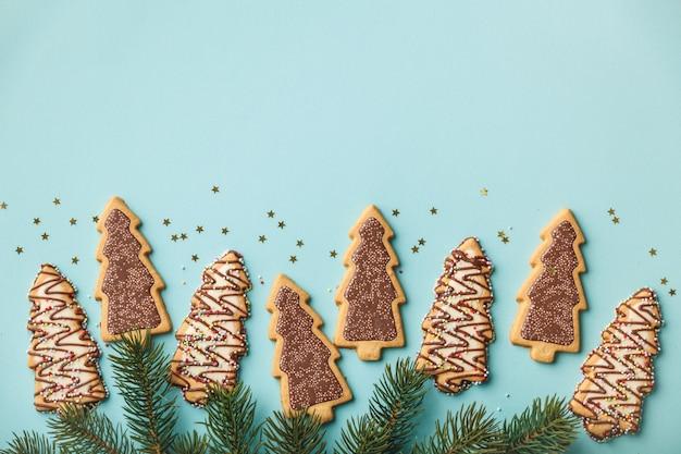 Galletas de jengibre navideñas en forma de árbol de navidad y ramas de árboles de navidad Foto Premium