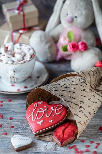 Galletas o galletas de jengibre en una caja de regalo con una cinta roja sobre una mesa de madera. día de san valentín. Foto Premium