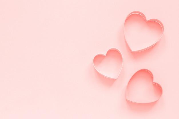 Las galletas rosadas de los cortadores en corazón forman en el fondo del rosa en colores pastel, colar entonado. amor romantico patron Foto Premium
