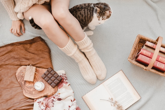 Gato caminando cerca de la mujer y libros sobre la cama | Foto Gratis
