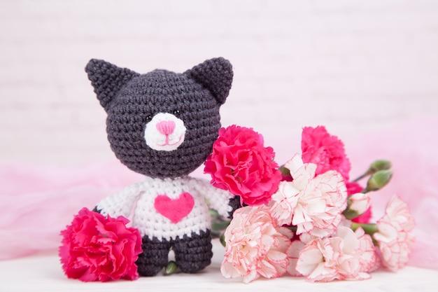 Gato de punto con un corazón. decoración de san valentín. juguete de punto, amigurumi. tarjeta de felicitación del día de san valentín. Foto Premium