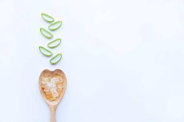 Gel de aloe vera en forma de corazón de cuchara de madera con rodajas de aloe vera sobre fondo blanco. Foto Premium