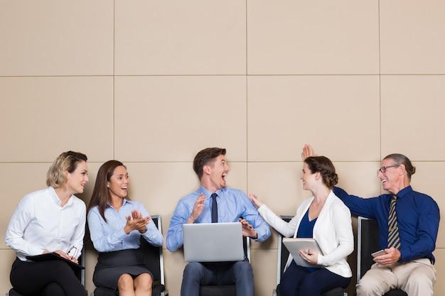 La gente alegre de negocios que felicita hombre joven Foto gratis