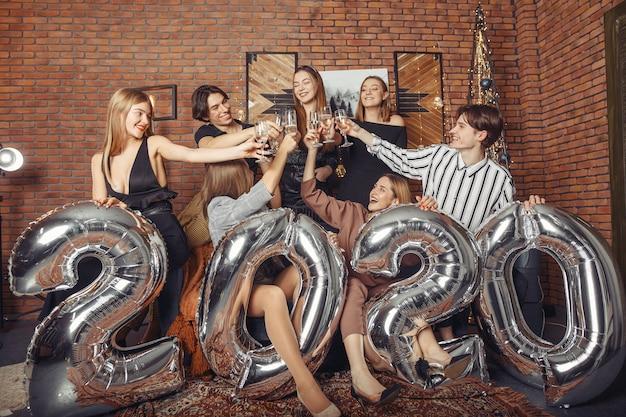 Gente celebrando un año nuevo con grandes globos Foto gratis