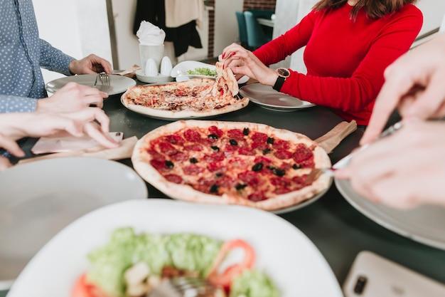 Gente comiendo pizza en un restaurante Foto gratis