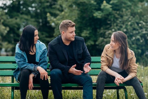 Gente conflictiva sentada en un banco y hablando Foto gratis