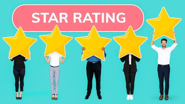 Gente diversa mostrando el símbolo de clasificación de estrellas doradas Foto gratis