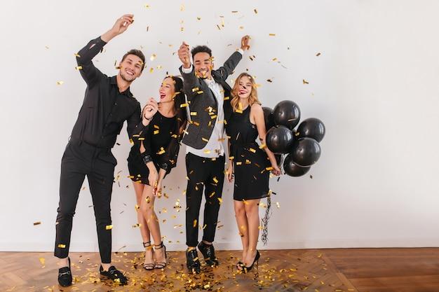 Gente divirtiéndose en la fiesta con globos negros y confeti. Foto gratis