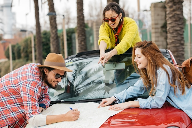 Gente, escritura, en, mapa de carreteras, con, lápiz, en coche Foto gratis