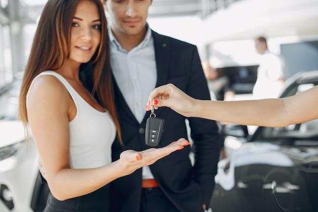 Gente con estilo y elegante en un salón de autos Foto gratis
