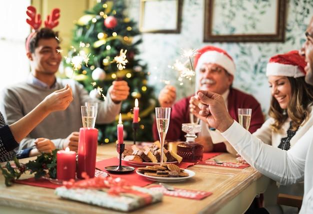 Gente feliz con fuegos de bengala encendidos en mesa festiva Foto gratis