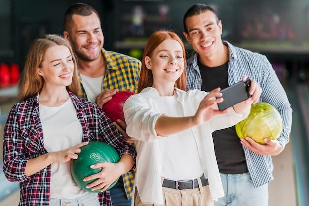 Gente feliz posando en un club de bolos Foto gratis