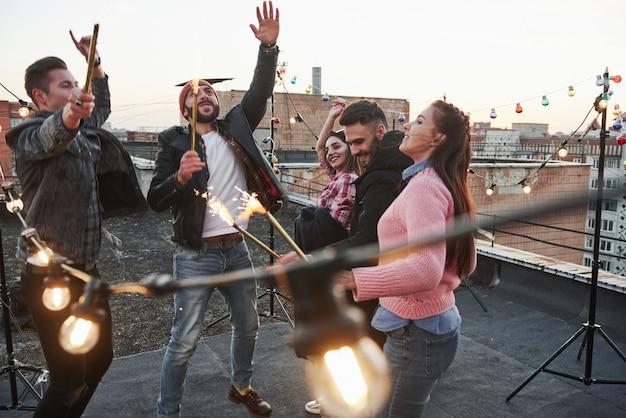 Gente guapa. jugando con bengalas en la azotea. grupo de jóvenes amigas hermosas Foto gratis