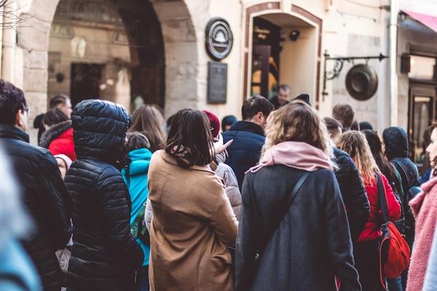 La gente hace cola en la cola, se arrastra en una cola de entorno urbano de personas Foto Premium