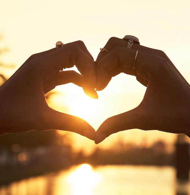Gente haciendo un corazón con las manos al atardecer Foto gratis