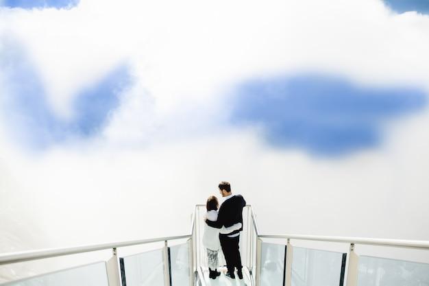 Gente hermosa abrazo en el cielo y las nubes Foto gratis