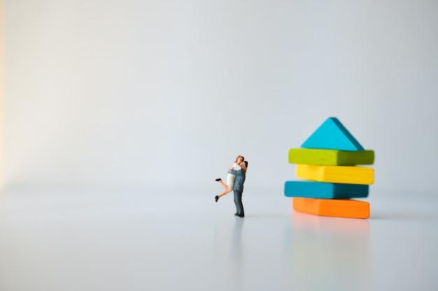 Gente en miniatura, amante abrazándose con un fondo de rompecabezas tangram Foto Premium
