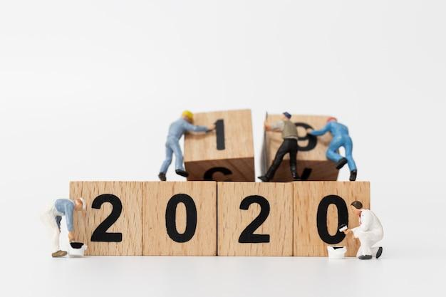 Gente en miniatura: el equipo de trabajadores crea el bloque de madera número 2020 Foto Premium