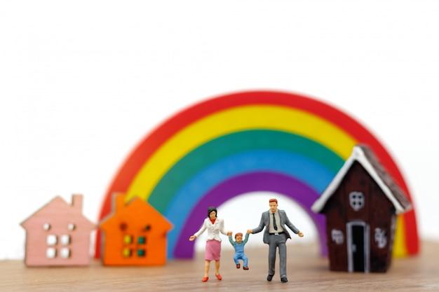Gente en miniatura: familia y niños disfrutan con casa y arcoiris. Foto Premium