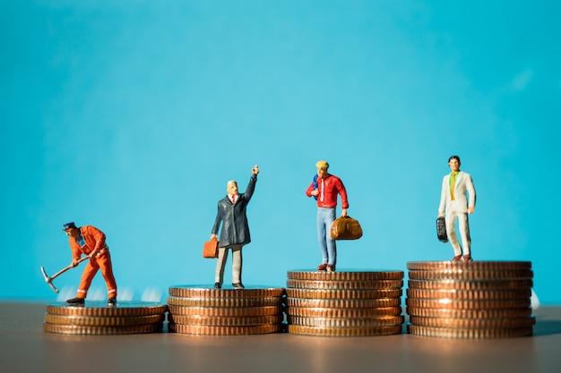 Gente miniatura, grupo de hombre de negocios de pie en monedas de pila Foto Premium