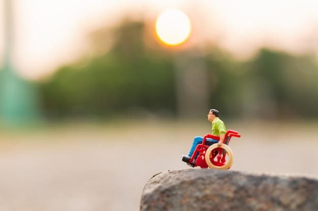 Gente en miniatura: hombre discapacitado sentado en silla de ruedas. Foto Premium