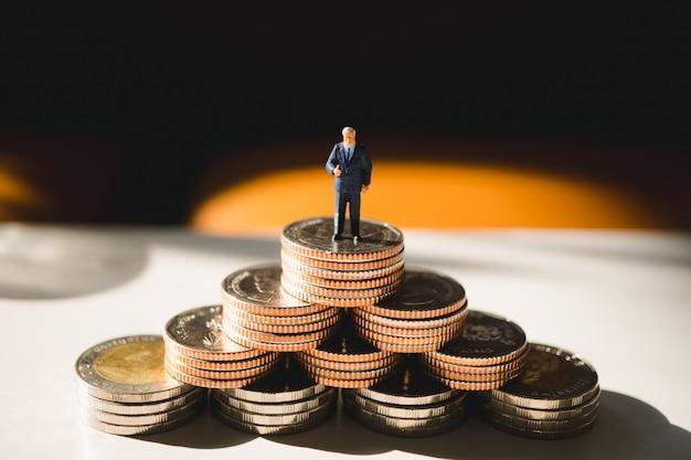Gente en miniatura, hombre de negocios de pie en la pila de monedas Foto Premium