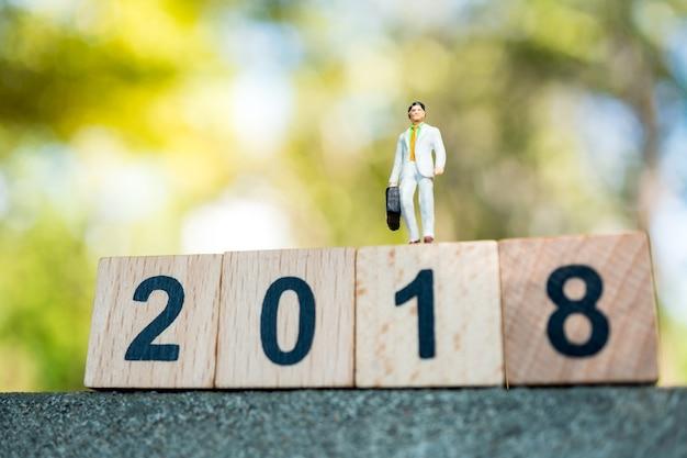 Gente miniatura, hombre de negocios que se coloca en bloque de madera del año 2018 usando como negocio, financiero y le Foto Premium
