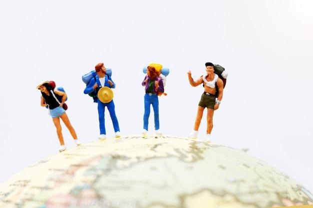 Gente en miniatura, mochileros en el mundo caminando hacia el destino. Foto Premium
