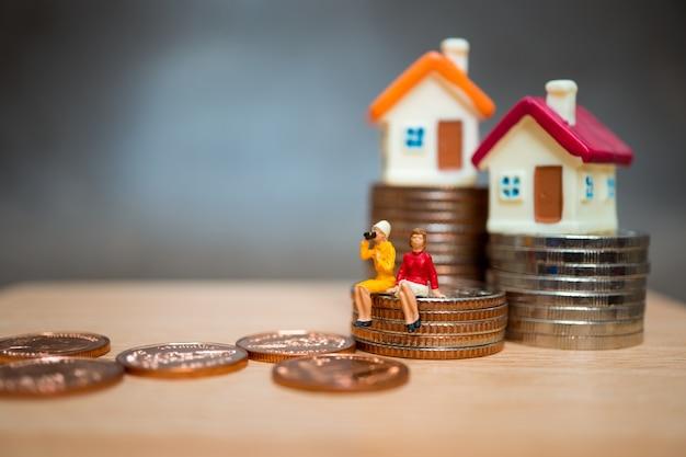 Gente miniatura, pareja mujer sentada en monedas de pila y mini casa Foto Premium